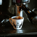 white and black ceramic mug on black and silver coffee maker